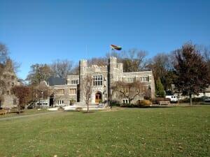 Large gothic grey stone building with rainbow flag flying
